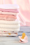 Pink Pacifier and Baby Clothes Stock Photo