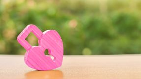 A pink padlock in shape of a heart. Heart health. The secret of relationships and the rules of a strong family. Strong love affair. Secrets, rumors and gossip stock images