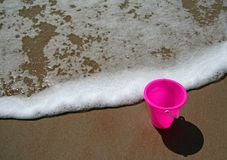 Pink pail at the beach. Pail sitting in the sand at the beach as a wave approaches royalty free stock images