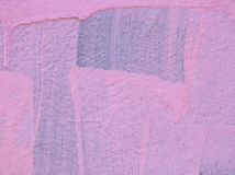 Pink paint on a wall with drips and brush marks with the original blue color showing underneath. Streaky faded pink paint on a wall with drips and brush marks stock photos