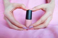 Pink Painted Nails. Beautiful Pink Nail Manicure with Pink Bottle in Woman is Hand on Pink Background. Great for Any Use royalty free stock photo