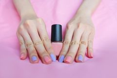 Pink Painted Nails. Beautiful Pink Nail Manicure with Pink Bottle in Woman is Hand on Pink Background. Great for Any Use stock photography