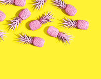 Pink painted pinapples. On a vivid yellow background Royalty Free Stock Images