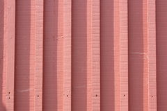 Pink painted wood panelled fence background. A panelled outdoor fence painted pink.  Shadow from the sun Royalty Free Stock Image
