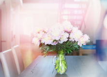 Pink pale peonies bunch on dining table in apartment.  Home Interior. Royalty Free Stock Image