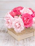 Pink and pale pink roses bouquet in the wooden box. Tied with jute rope Stock Photo