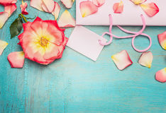 Pink pale shopping bag with rosa flowers and petal on blue turquoise shabby chic background, top view, place for text, border Stock Photography