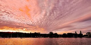 Pink Panoramic Sunrise Seascape Australia. A Pastel Pink colored cloudy sunrise seascape panorama, over sea water with water reflections. Queensland, Australia Royalty Free Stock Photo