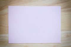 Pink paper blank on the brown wooden floor of vintage color. Royalty Free Stock Photography