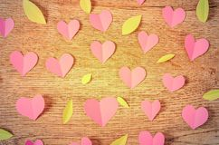 Pink paper cut heart shape and leaf. Pink paper cut heart shape and leaf on wooden background Stock Images