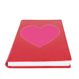 Pink paper heart on red book isolated on white. Background ,selective focus Royalty Free Stock Photography