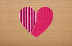 Pink paper hole in brown cardboard Stock Images