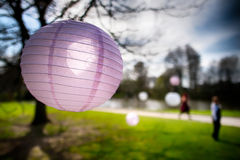 Pink paper lantern / bauble, with others blurred out in the background and sun shining through. Pink paper lantern / bauble hanging from a tree, with other Royalty Free Stock Photo