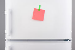 Pink paper note attached with green sticker on refrigerator Stock Photography