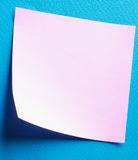 Pink paper note on blue background Stock Photography