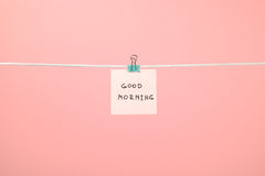 Pink paper note on clothesline with text Good Morning Stock Images