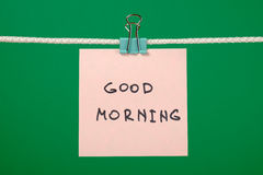 Pink paper note on clothesline with text Good Morning Royalty Free Stock Photography