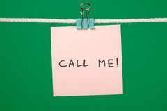 Pink paper note on the string with text Call Me! Stock Photography