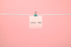Pink paper note on the string with text Call Me! stock image