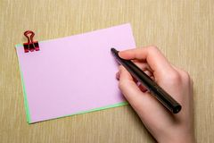 pink paper with paperclip and woman hand holding a pen about to write. Objects isolated on yellow Royalty Free Stock Photo