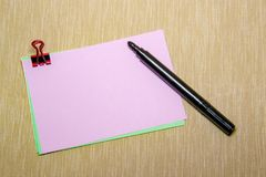 pink paper with paperclip and woman hand holding a pen about to write. Objects isolated on yellow Royalty Free Stock Photos