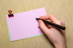 pink paper with paperclip and woman hand holding a pen about to write. Objects isolated on yellow Stock Photos