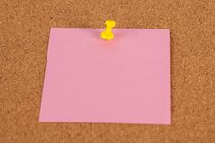 Pink paper pined with yellow tack on brown cork board background.  Royalty Free Stock Images