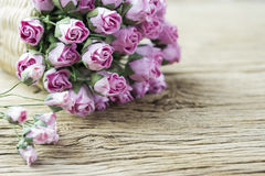 Pink paper rose in weave basket on old wood Stock Photos