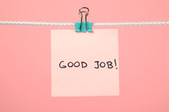 Pink paper sheet on the string with text Good Job royalty free stock images