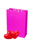 Pink paper shopping bag and two red heart isolated on white Royalty Free Stock Photo