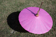 Pink paper umbrella. Placed on grass Stock Photos