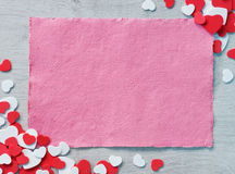 Pink paper on wooden table among decorative red and white hearts. Royalty Free Stock Images