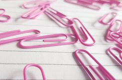 Pink paperclips scattered on white lined paper Royalty Free Stock Photos