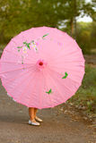 Pink parasol with little girl's legs and feet showing from behind Stock Photos