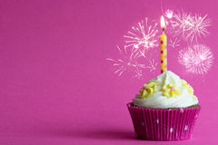 Pink party cupcake. Pink cupcake with yellow burning candle and fireworks on pink background Royalty Free Stock Images