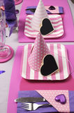 Pink party hats on table setting - vertical. Pink and purple theme party table setting decorations, with pink stripe square plates, pink polka dot and strip Royalty Free Stock Photo
