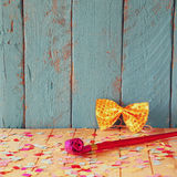 Pink party whistle on wooden table with colorful confetti. vintage filtered image Stock Photography