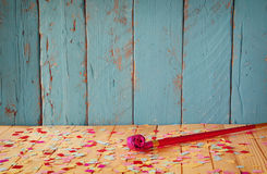 Pink party whistle on wooden table with colorful confetti. vintage filtered image Stock Images