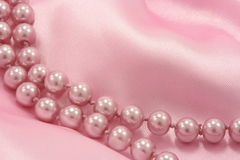 Pink pearls. On soft pink silk Royalty Free Stock Photography