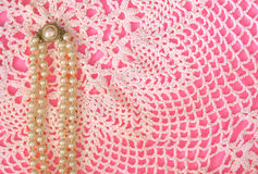 Pink, Pearls, Lace. Strand of pearls on lace doily on pink background Royalty Free Stock Photo