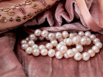 Pink pearls on pink velvet. Photo of pink pearls on pink velvet fabric background with sequins and beads Royalty Free Stock Image