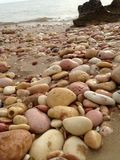 Pink pebbles on the beach. Pink rocks and pebbles mixed amongst sand and cream pebbles on the foreshore smooth and slightly wet at Pebble Beach near Exmouth in Stock Photo