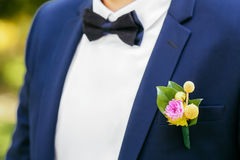 Pink peon boutonniere pinned to a grooms jacket Royalty Free Stock Image