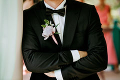 Pink peon boutonniere pinned to a grooms jacket Stock Image
