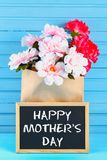Pink peonies in a craft package with a chalkboard on a blue wooden table. Postcard for the holiday. Happy mother`s day.  Royalty Free Stock Photography