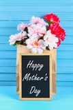 Pink peonies in a craft package with a chalkboard on a blue wooden table. Postcard for the holiday. Happy mother`s day.  Royalty Free Stock Photo