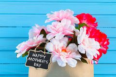 Pink peonies in a craft package with a chalkboard on a blue wooden table. Postcard for the holiday. Happy mother`s day.  Stock Photo