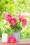 Pink peonies in metal vase and empty card for letter Stock Photo