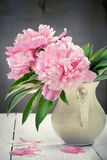 Pink peonies in retro vase on wooden table, vintage colors, tone Royalty Free Stock Photo