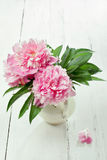 Pink peonies in retro vase on wooden table Stock Images